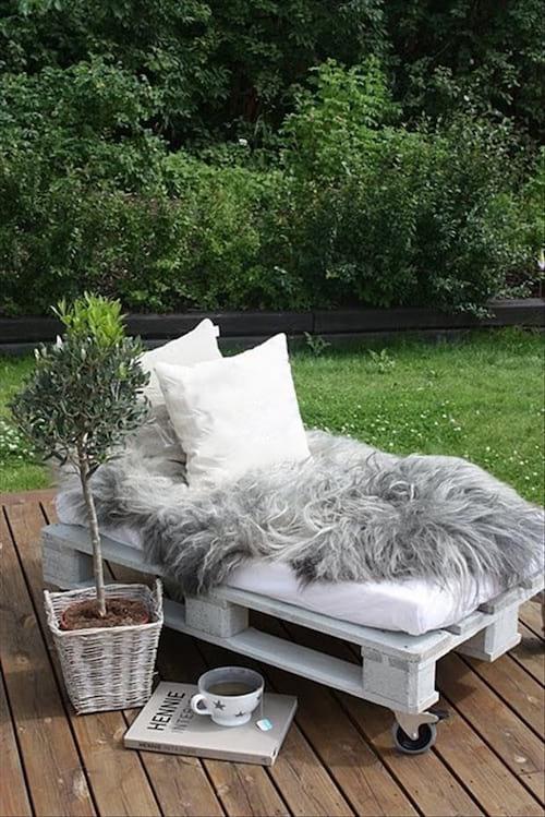 Petit siège blanc en extérieur avec une palette blanche