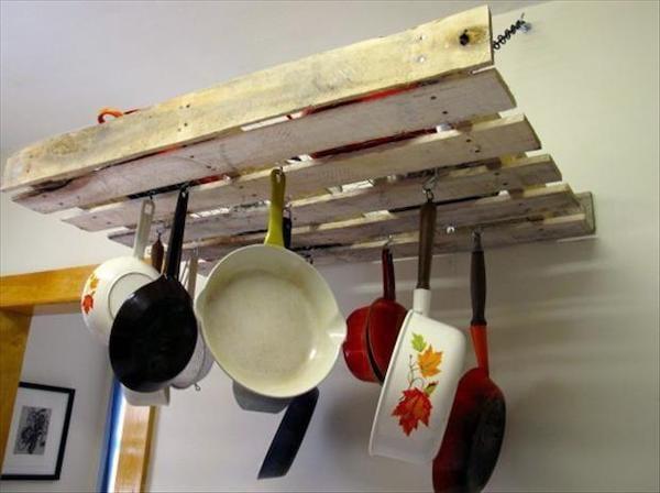 Une palette accrochée au mur à l'horizontale et qui sert de rangement pour des ustensiles de cuisine