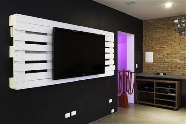 Télévision accrochée au mur avec une grande palette blanche en support