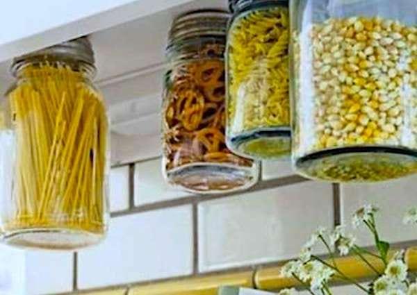 Utilisez des bocaux suspendus sous les meubles hauts pour gagner de la place dans votre cuisine.
