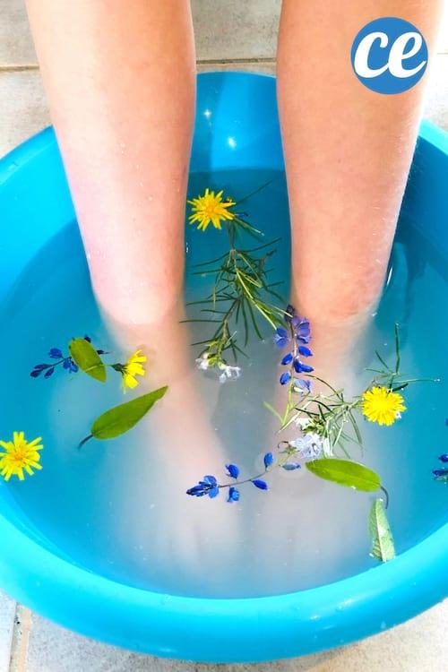 bain de pieds relaxant fait maison avec du sel d'Epsom, du bicarbonate et des fleurs dans une bassine bleue