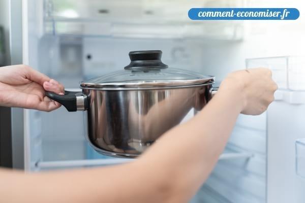 Une femme qui met une casserole chaude dans le réfrigérateur.