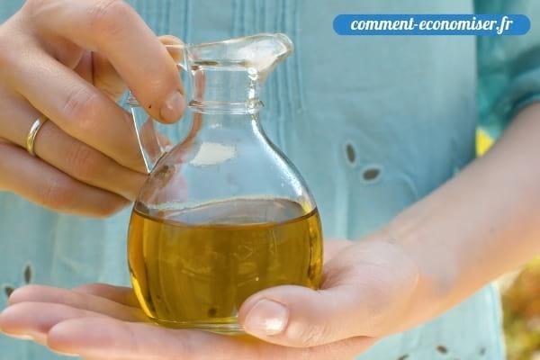 Une femme qui tient une bouteille d'huile d'olive dans une bouteille en verre.