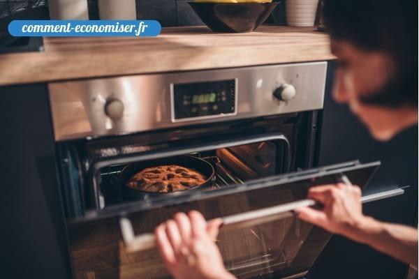 Une femme qui vérifie la cuisson d'un gâteau en ouvrant le porte du four.