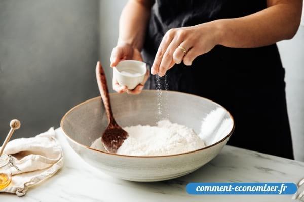 Une femme qui ajoute une pincée de sel dans la farine avant de faire une pâte à tarte.