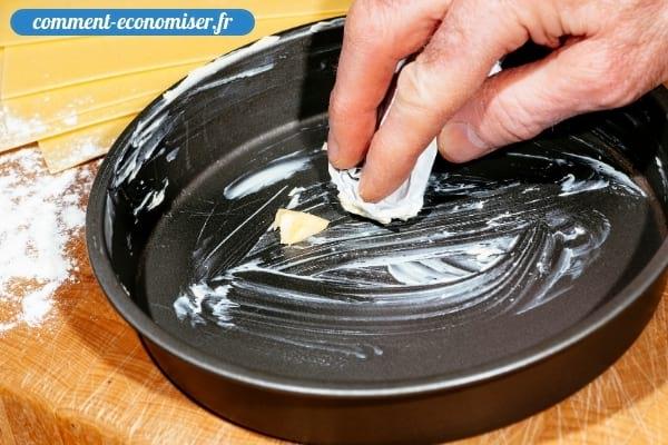 Une main qui étale du beurre à l'intérieur d'un moule à gâteau.