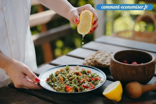 Une main qui ajoute un filet de jus de citron pressé dans un plat.