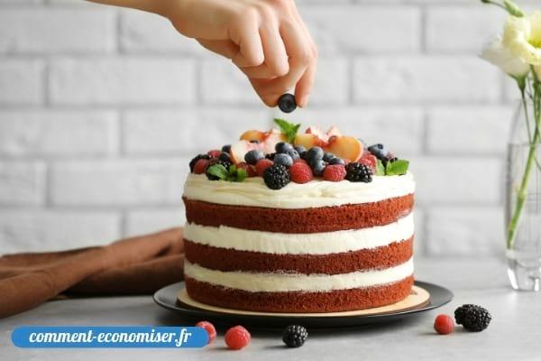 Une main qui décore un gâteau fait maison.