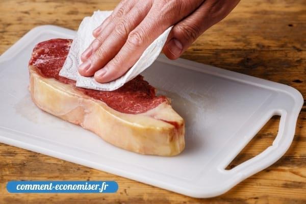 Une main qui sèche de la viande avec un essuie-tout.