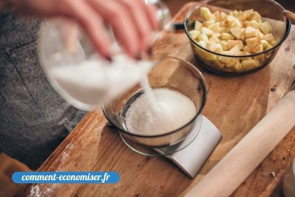 Une main qui pèse du sucre avec une balance de cuisine.