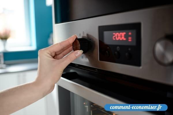 Une main qui règle la température pour préchauffer le four.