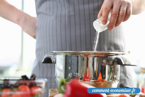 Une main qui ajoute du sel dans une casserole d'eau.