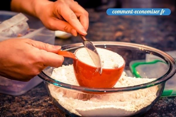 Une main qui nivèle la farine dans un tasse.
