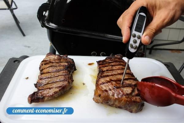 Une main qui vérifie la cuisson de la viande avec un thermomètre.