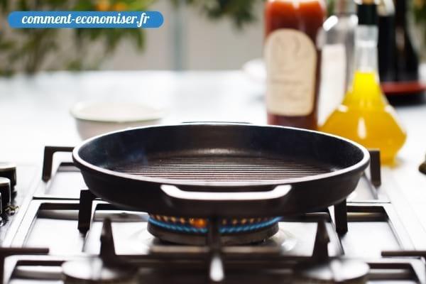 Une poêle en train de chauffer sur la plaque de cuisson d'une cuisine.