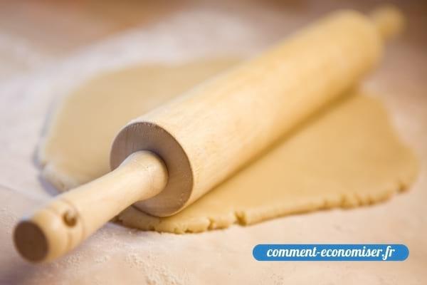 Un rouleau à pâtisserie et de la pâte brisée.