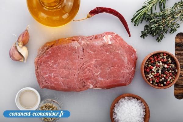 Une pièce de viande de bœuf crue et ses ingrédients pour l'assaisonner.