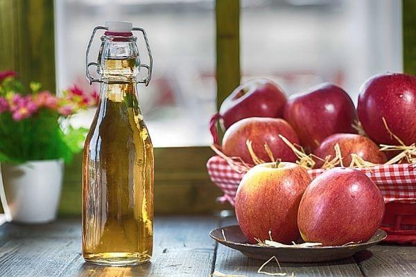 bouteille de vinaigre de cidre et pomme rouges