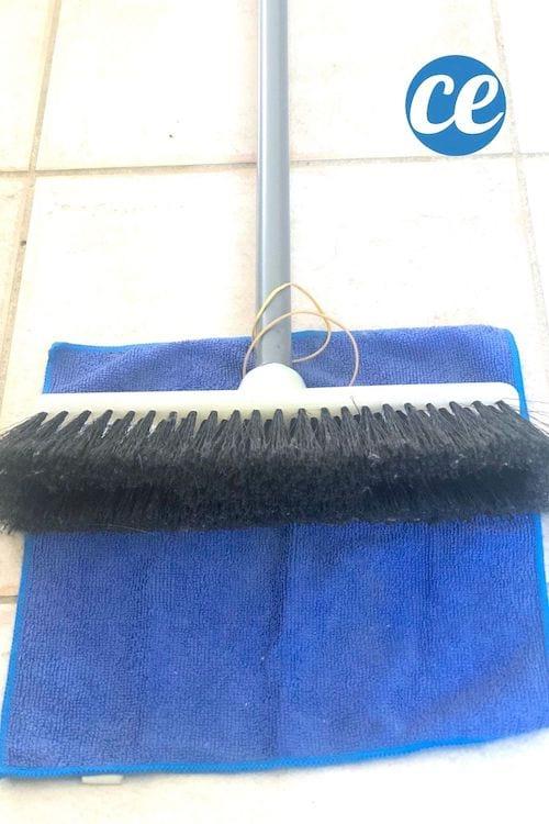 Un balai posé sur un chiffon microfibre bleu avec deux élastiques pour nettoyer les plinthes