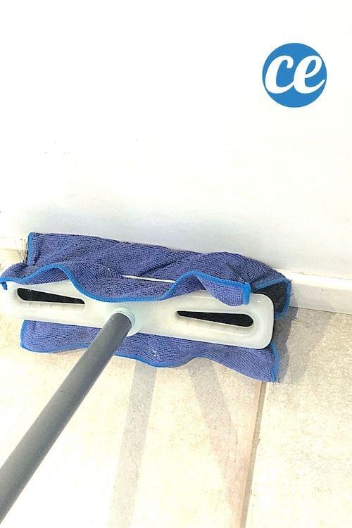 La brosse d'un balai recouvert par un chiffon tenu par un élastique pour nettoyer les plinthes sans se baisser