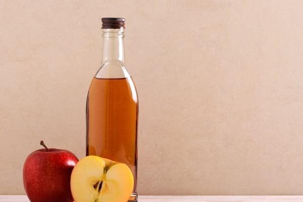 Une bouteille de vinaigre de cidre avec 2 pommes pour soulager piqure insectes