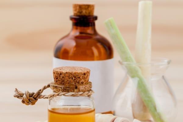 Flacons huiles essentielles de citronnelles posés sur une table pour faire fuir les mouches