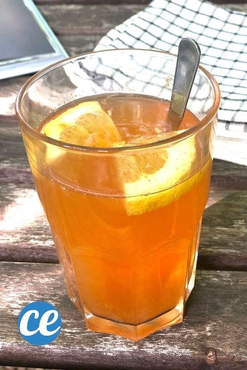 Un verre de boisson détox fait maison avec du citron sur une table en bois avec des torchons
