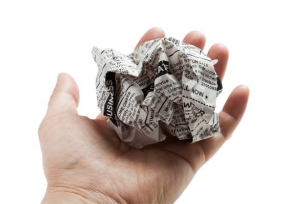 Une boule de papier journal dans une main pour nettoyer parois vitrées de douche