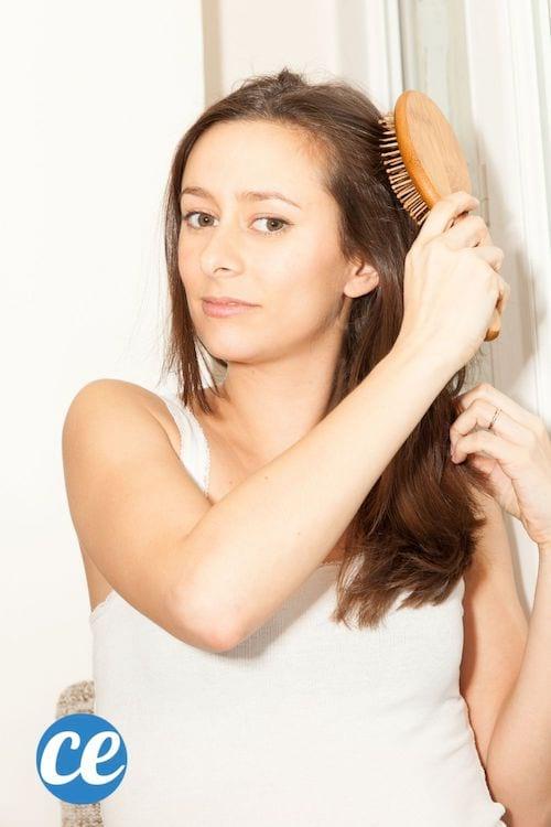 Une femme en débardeur se brosse les cheveux avec une brosse à picots