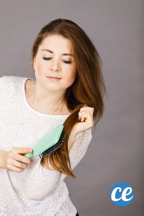 Une femme aux cheveux châtains longs se brosse les cheveux avec une brosse plate à picots