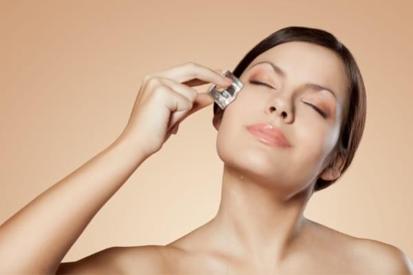 Une femme qui passe un glaçon sur le visage pour avoir un teint éclatant
