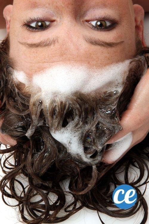 Une femme se lave les cheveux la tête à l'envers