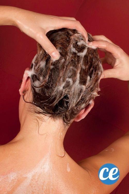 une femme se lave les cheveux en se massant le cuir chevelu