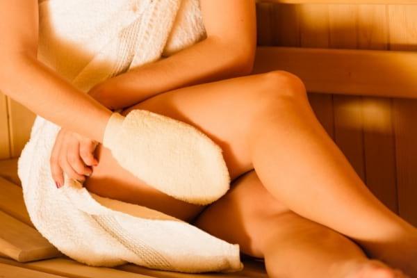 Un gant de toilette exfoliant sur une jambe de femme pour enlever peau morte