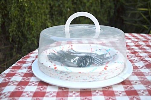 Des assiettes et ustensiles de camping dans une boîte à gâteau sur une nappe à carreau.