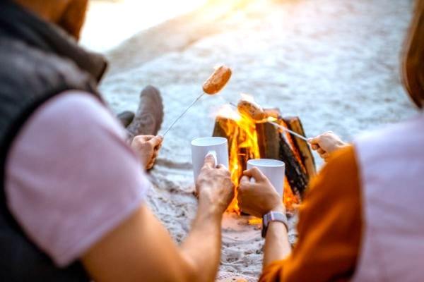 Astuce camping : faites griller des saucisses avec des pics à brochettes en métal.