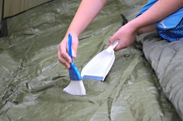 Astuce camping : nettoyez l'intérieur de la tente avec une balayette.