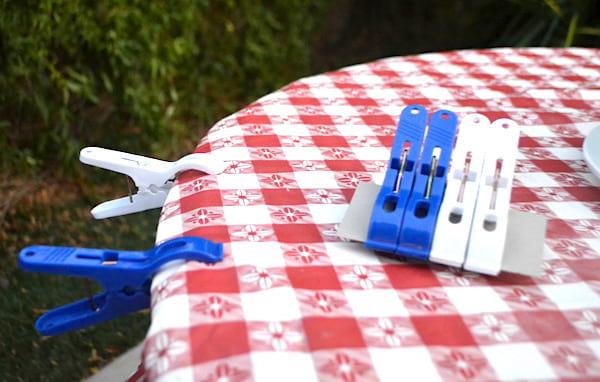 Astuce camping : utiliser des pinces à linge pour maintenir la nappe en place.