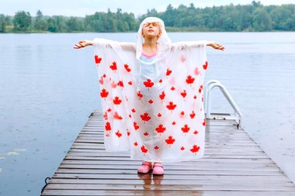 Une petite fille avec un poncho de pluie en camping.