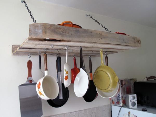 des casseroles suspendus à une palette dans une cuisine