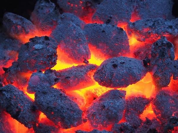 la chaleur brûle les résidus de viande sur la grille de bbq pour la rendre propre