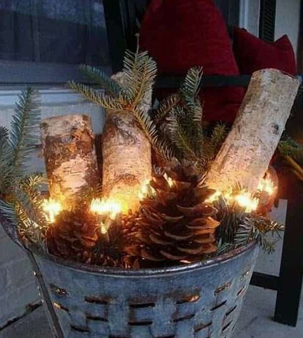 un sceau rempli de pommes de pin et de bûches pour Noël