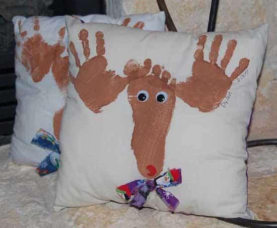un coussin décoré avec des empreintes de pieds et de mains pour noel
