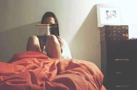 Femme en train de lire un livre au lit