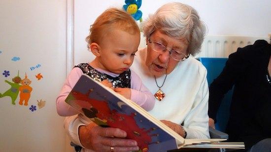 une grand-mère et son petit fils lisent un livre