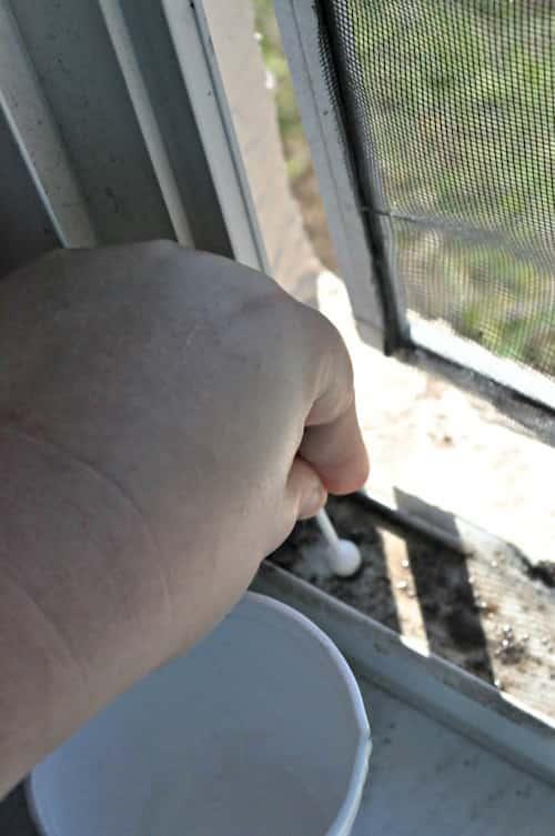 Pour nettoyer les rails de fenêtres sans effort, versez du bicarbonate et du vinaigre blanc dessus et frottez avec des Coton-Tige.