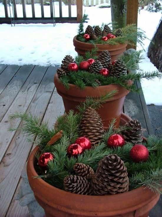 des pots remplis de pommes de pin pour décorer l'entrée