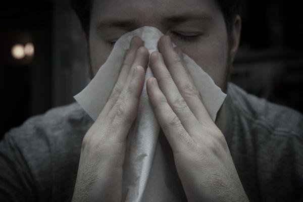 Homme qui se mouche avec un mouchoir en papier à cause des allergies