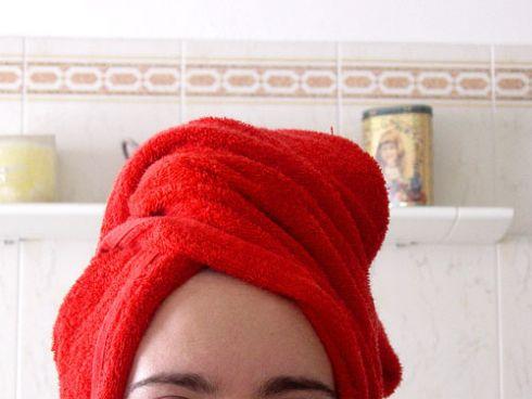 Serviette rouge sur la tete après s'être lavé les cheveux