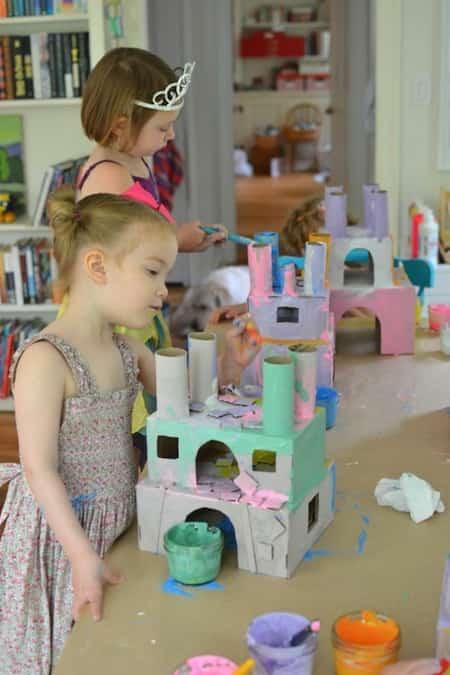des petites filles fabriquent un château avec des rouleaux de papier toilette vides